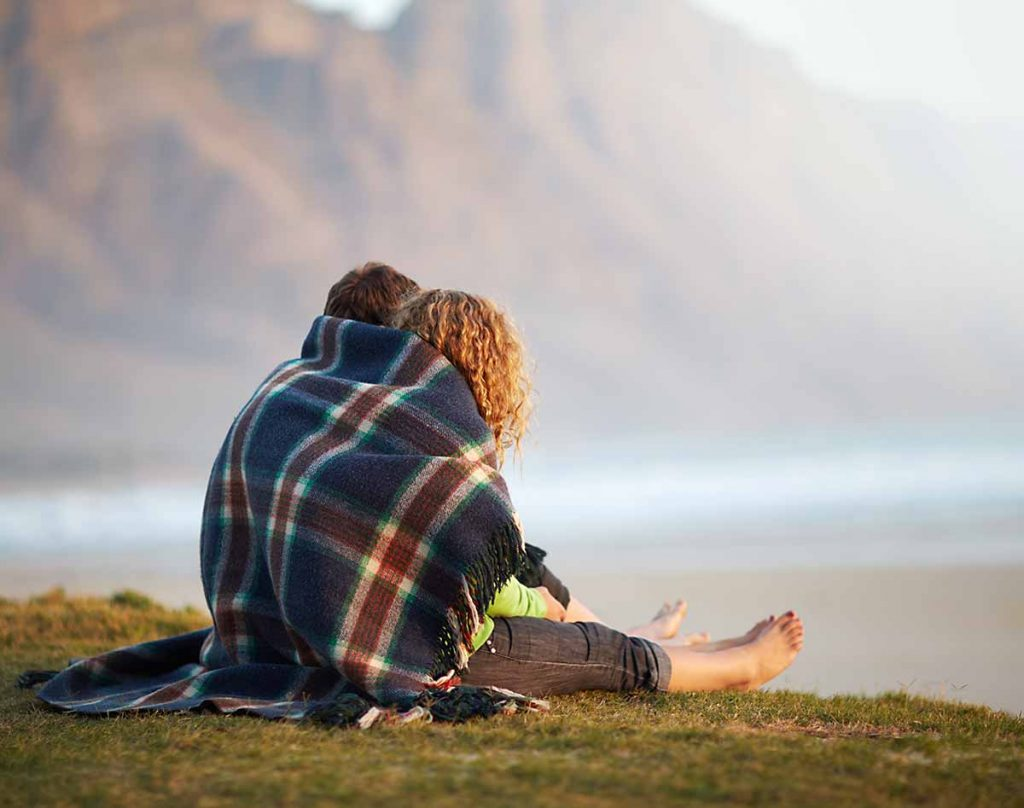 Couple sit under blanket planning their future