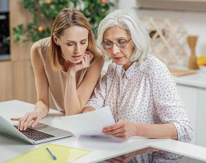 Elderly mother and daughter reviewing Will and paperwork