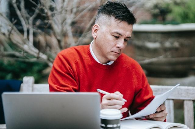 Man in red checking paperwork